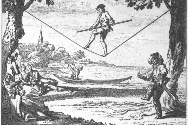 Black and white photo of man balancing on a tightrope