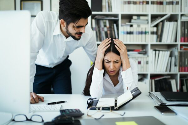 Upset employee and angry boss leaning over