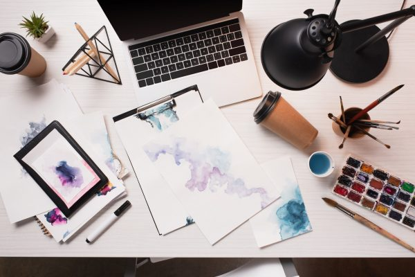 flat lay of messy office desk with laptop, sketches and art supplies