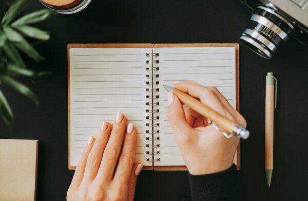 Flat lay woman's hand writing down