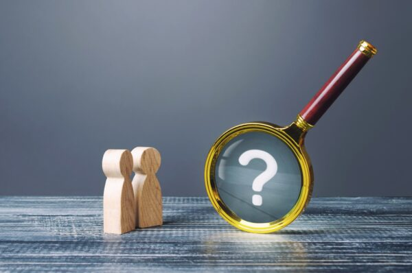 Two wooden figures with magnifying glass