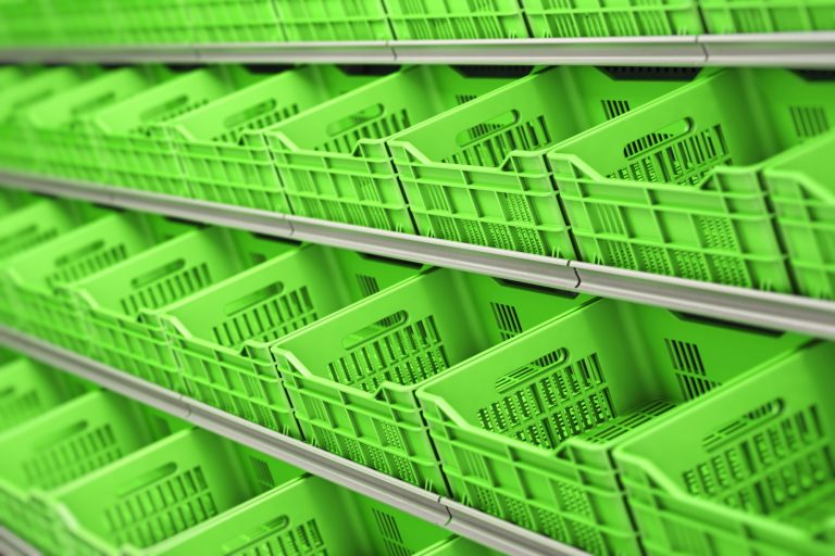 Plastic vegetable and fruit crates in a row on supermarket shelves.