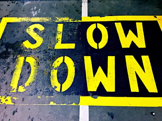 """Street sign painted on the road """"SLOW DOWN"""""""