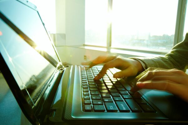 Side view of hands on a keyboard typing