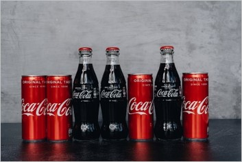 4 cans and 3 bottles of Coca Cola lined up