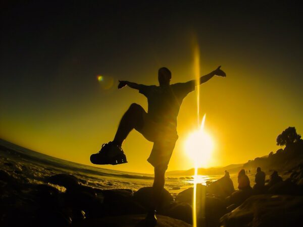 Shadow of a man doing Karate Kid pose in front of a sunset