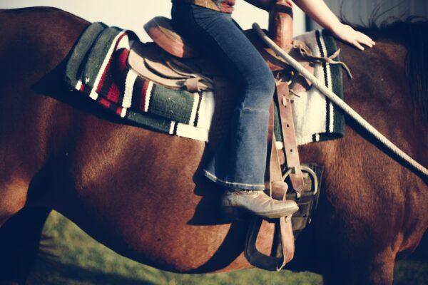 Close up feet in stirrups riding a horse