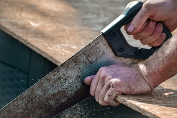 Close up of man's hands using a saw on a wooden plank