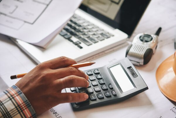 Calculating estimate using a calculator at an office desk