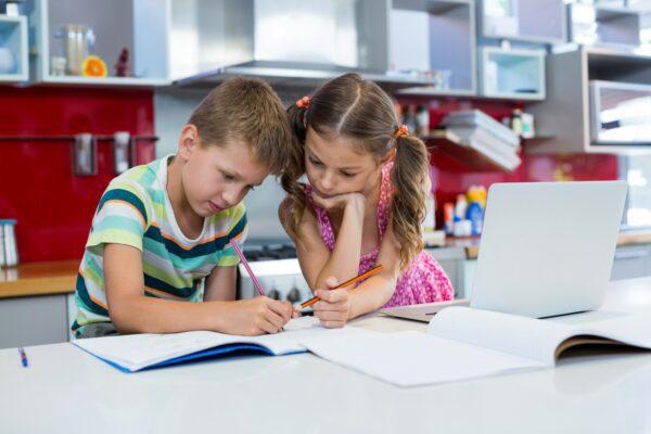 Two children doing homework in a kitchen