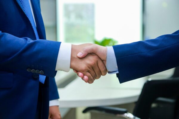 To deal withBusiness people shake their hand before negotiation