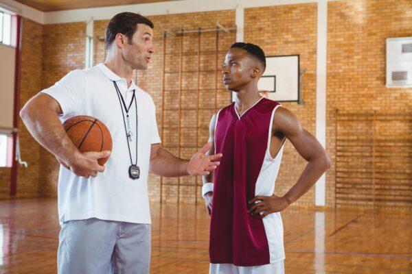 Coach guiding basketball player